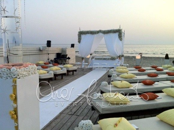 Matrimonio estivo in spiaggia baciato dalla brezza del mare con i colori del tramonto