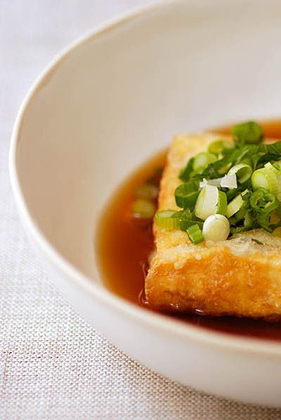 """AGEDASHI TOFU aka AGE TOFU ~~~ deep-fried tofu served in a dashi and soy sauce-based sauce. accompaniments most often include scallion and grated daikon. this post's link leads to a recipe shared from the book, """"harumi's japanese cooking"""". [Japan] [spoonfulblog]"""
