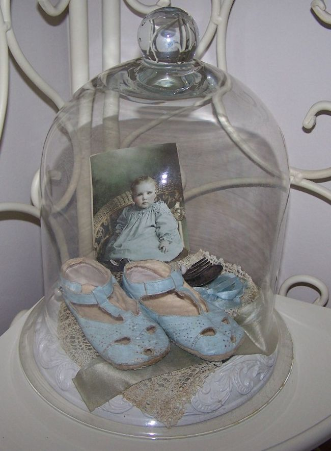 Arrange inside a cloche, baby shoes on appropriate fabric, along with a photo of the baby the shoes belong to.