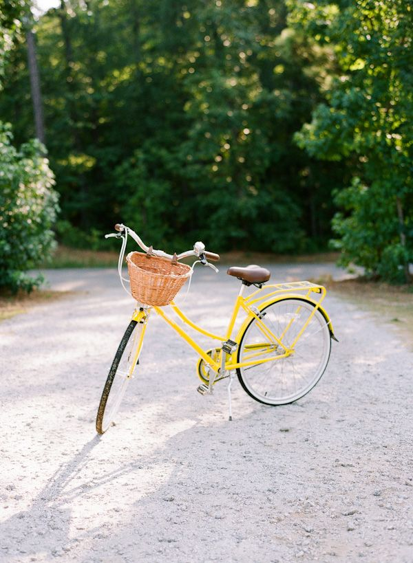 A yellow bicycle in summer, with a basket. Just need a loaf of bread, a French baguette, and flowers.