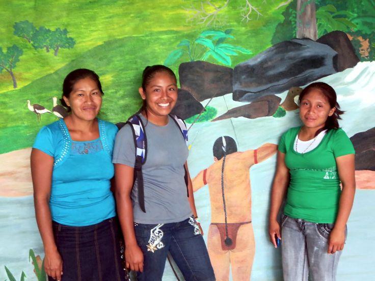 Three Makushi girls pose before a mural at Annai village near Rock View Lodge in central Guyana.