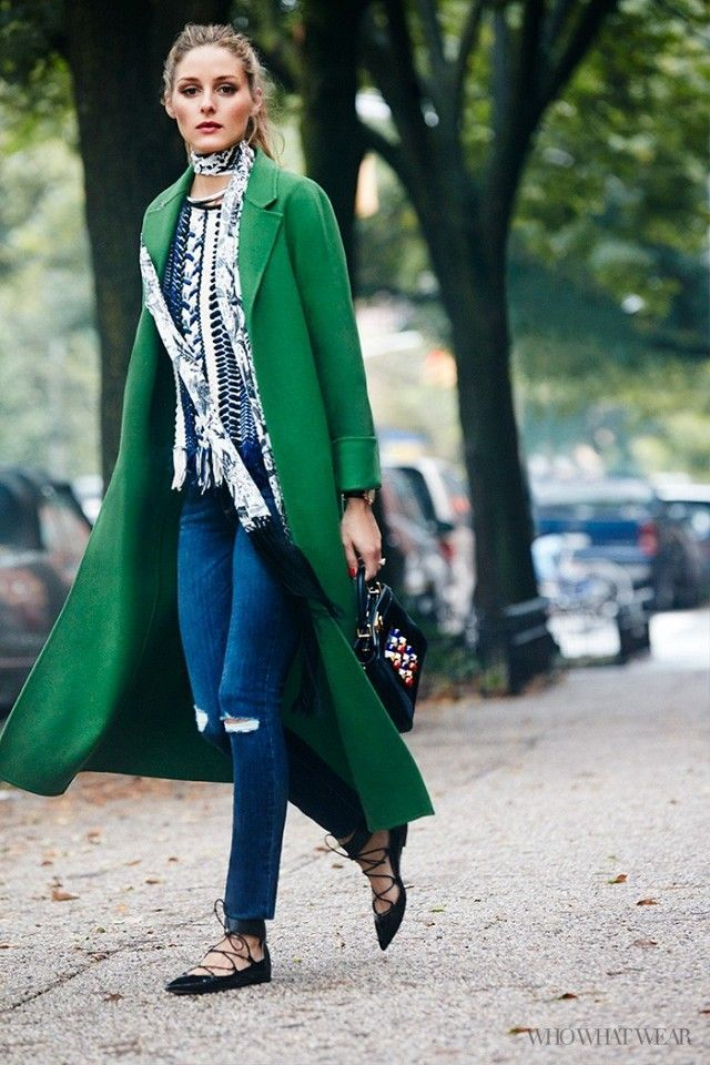 Olivia Palermo wears a green coat with a printed blouse, a skinny scarf, jeans, lace-up flats and a beaded handbag.