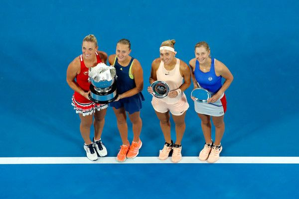 - (L-R) Timea Babos of Hungary and Kristina Mladenovic of France pose for a photo with the championship trophy and Elena Vesnina of Russia and Ekaterina Makarova of Russia pose with the runner-up trophy after the women's doubles final on day 12 of the 2018 Australian Open at Melbourne Park on January 26, 2018 in Melbourne, Australia.