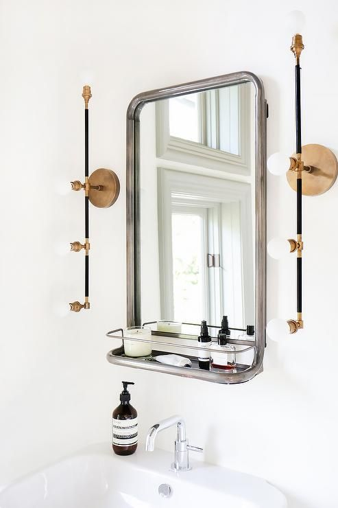 Modern bathroom features a Restoration Hardware Astoria Mirror with Shelf illuminated by brass linear sconces, Apparatus Studio Vanity Sconces, over a pedestal sink.