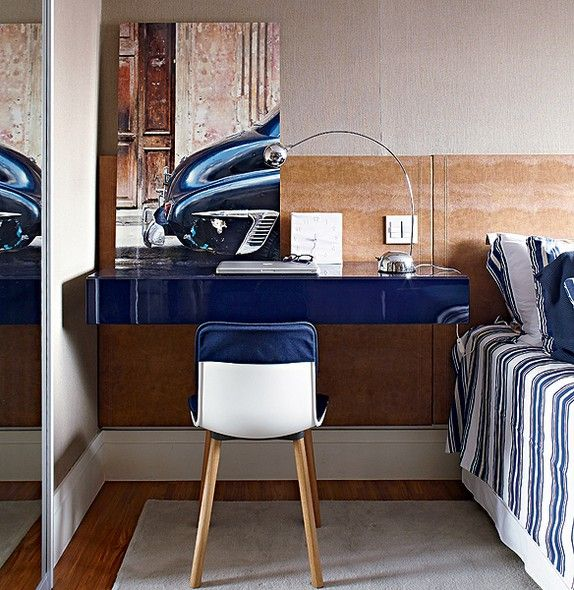 A cabeceira se estende pela lateral da cama para servir de fundo à escrivaninha, no canto de trabalho projetado pelo arquiteto Nelson Kabarite. Na bancada azul, tom presente em todo o quarto, ficam o computador e fotografia de Lufe Gomes