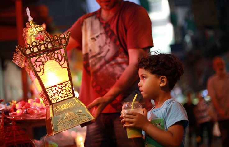Observing Ramadan | A Palestinian boy looks at a traditional Ramadan lantern in a street market in Gaza City, on July 6, 2013. | The Atlantic/ Mohammed Abed/AFP/Getty Images