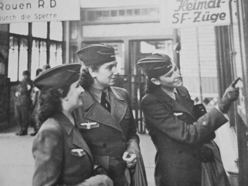 Three auxiliary employees of the communication services of the Wehrmacht look at the train schedule at the central railway station in the French city of Rouen.