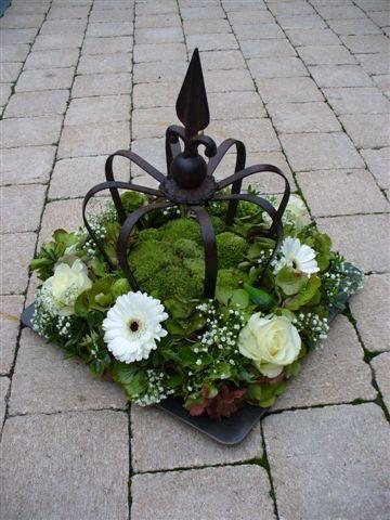 Afbeelding 055 by Elshout Pompoenen en Groendecoratie Bruinisse, via Flickr bord met een metalen kroon, met bloemstuk van mos en bloemen