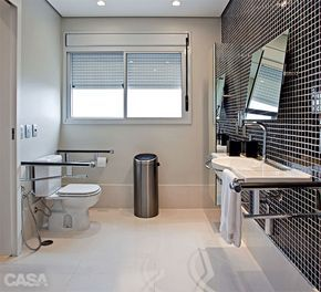 O espelho possui controle de inclinação lateral. A altura mínima em relação ao piso é de 1,10 m, e a máxima, 1,80 m. A pia também oferece barra de segurança, além de torneira monocomando. Sob ela, a área está liberada. Ao redor do sanitário, as barras de segurança da Keuco (Metalbagno) contam com porta-papel. A lixeira traz sensor.
