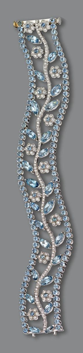 Auamarine and diamond bracelet.  Openwork serpentine band decorated with a central branch supporting flowers and leaves, set with marquise-shaped and round aquamarines as well as numerous small round diamonds, mounted in platinum, length 7¼ inches.