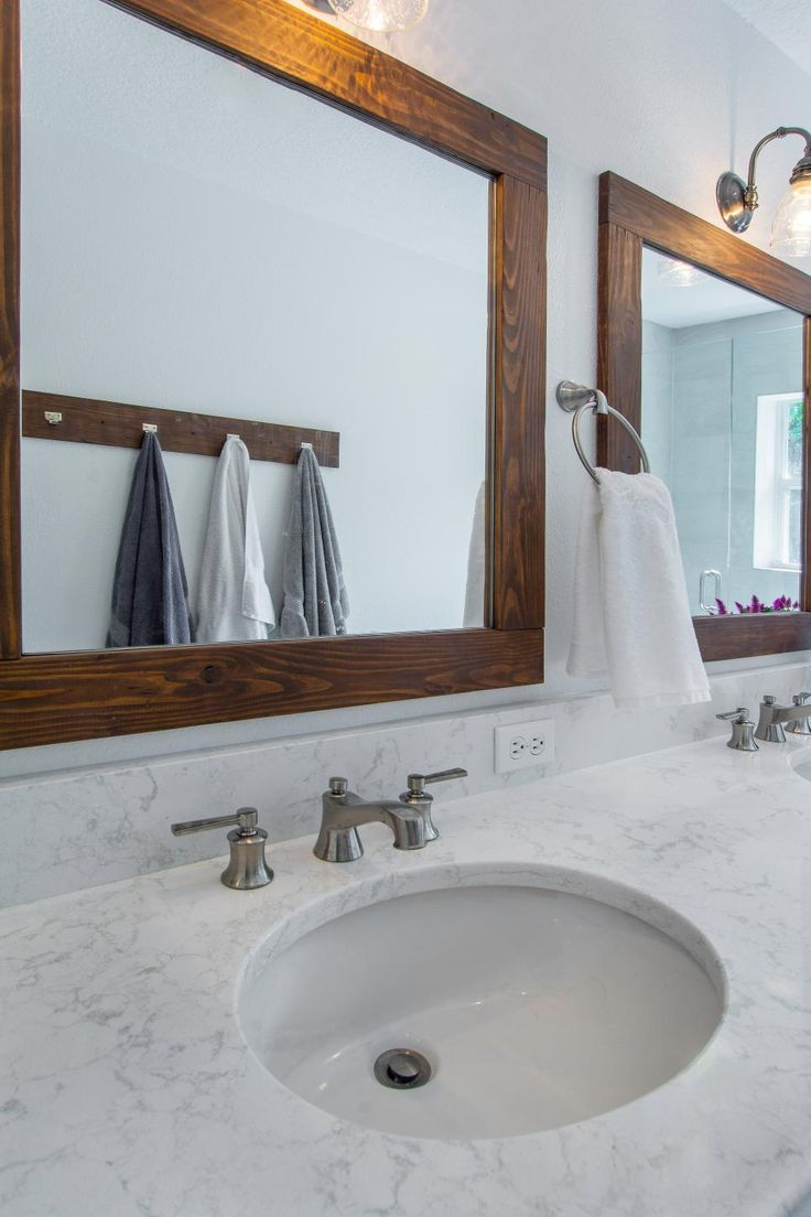 Wood frame mirrors help bring a natural touch as well as some warmth to this cool toned transitional bathroom with marble countertops.