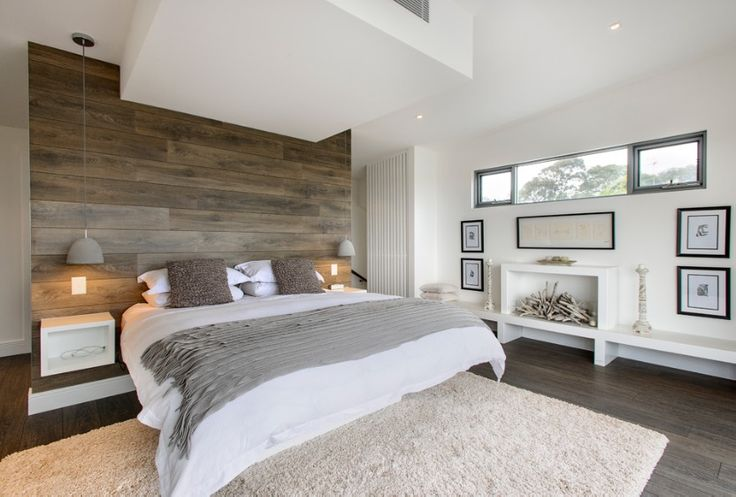 Natural and bright room. Feature wood headboard breaks up the use of white in the room. Pendant lighting either side of the bed hanging from the ceiling. Bedside cabinets attached to feature wall raised off from the ground