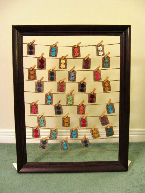 """""""This huge frame came from the thrift store for $4 and I hot glued twine strings to the sides so I could pin on my earring cards with mini clothespins. I found a couple bracket pieces at the hardware store for cheap so we screwed them on the bottom corners so it would stand."""""""
