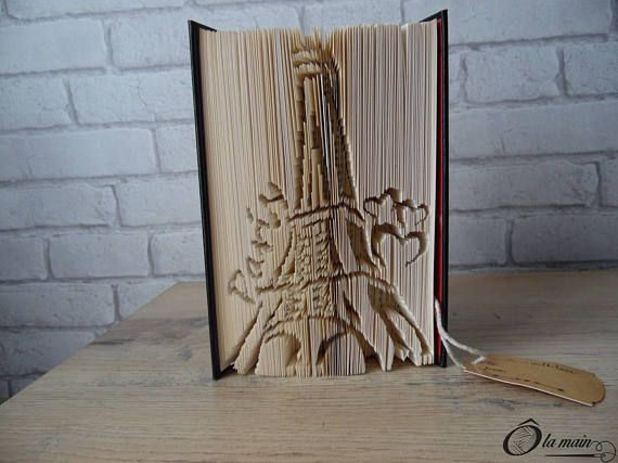 La collection A Livre Ouvert est une série de livres doccasion transformés en objets de décoration via plusieurs techniques (découpage, pliage ou décou-pliage). Chaque page est découpée et/ou pliée à la main pour donner vie à un motif.  Le modèle Paris Je taime est un livre découpé et plié pour représenter la Tour Eiffel accompagnée de coeurs et du mot Paris. Le livre possède une magnifique couverture bordeaux, noire et or agrémentée de coeurs. VENDU SEUL