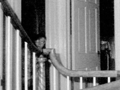This picture was taken by a professional photographer after George Lutz and his family fleed the house due to evil paranormal activity, if you watched the movie you know the story.  Ed & Lorraine Warren, founders of The New England Society For Psychic Research, were called in to examine the house. Gene Campbell, a professional photographer went in with Warrens team, he set up an automatic camera on the 2nd floor landing that shot off the boy ghost.  Some say evil spirits will disguise…