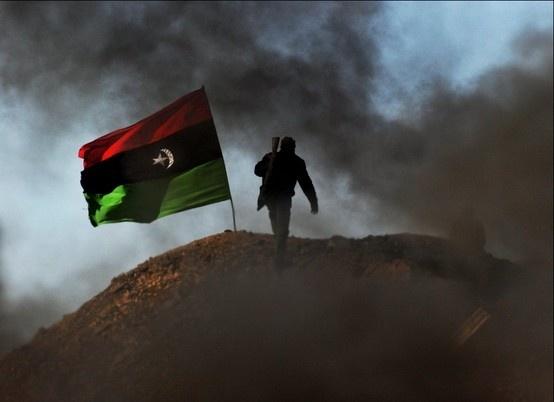 Man walking towards a Libyan flag