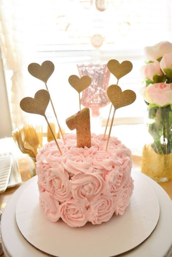 Make her first birthday party extra memorable with this adorable smash cake decorated with pretty pink rosettes and gold hearts. It's simple to make yourself and will look gorgeous alongside your party spread. Click to see the rest of this sweet party photoshoot!