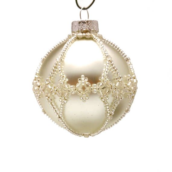 Shiny light silver bauble with crystal filigree pattern. (colour number: 113-513) This is an original pattern by Sine Hummel. Our baubles are made from real glass, and will add an elegant air to your tree or decorations. The beads give them a hint of antique or vintage. The baubles