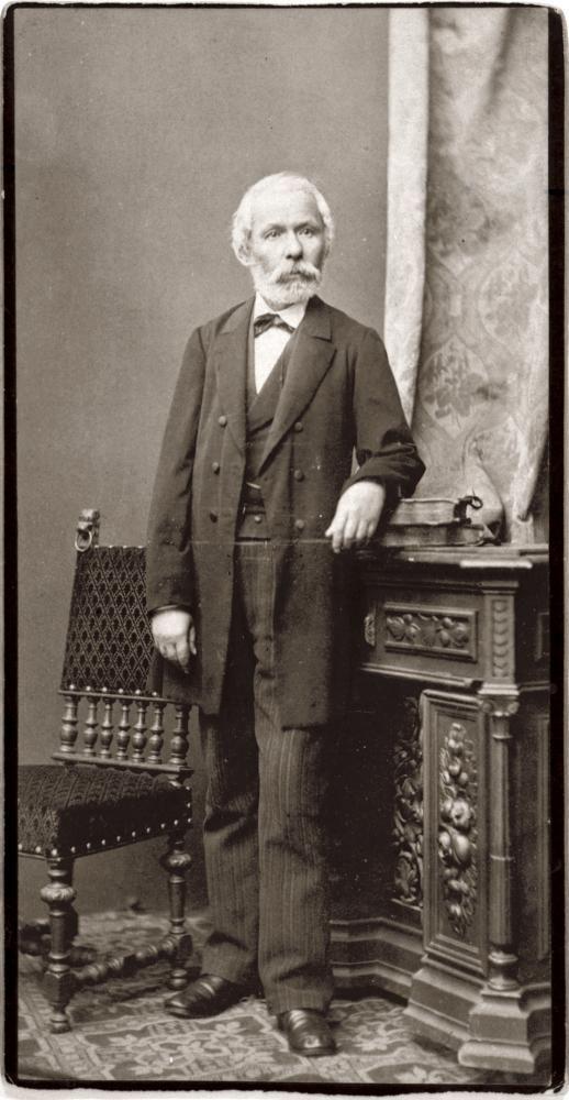 """Arany János utolsó fényképezkedése alkalmával, halála előtt két évvel készült ez a felvétel Ellinger Ede műtermében, több hasonló beállítással együtt. Közülük a legismertebb a """"botos és kalapos"""" portré, melyen az író szintén könyvekre támaszkodva áll, de kezében botot és kalapot tart. Erről írt Kosztolányi Dezső 1917-ben: """"Itt egy megható alakot bámulok, melyet alig-alig ismernek. A beesett, csontos arcot rövidre nyírt ősz szakáll keretezi, a hosszú haj csapzottan simul előre, a halántékra…"""