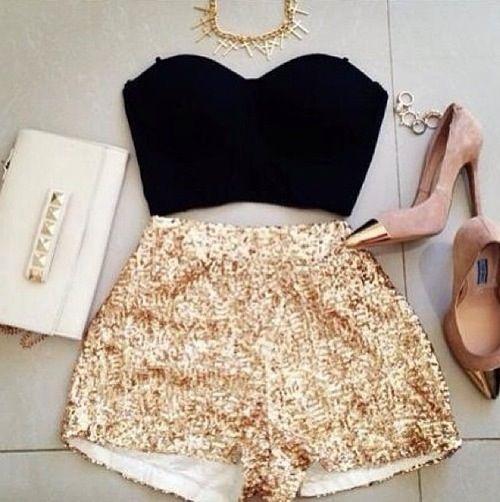 Outfit de short dorado con top negro, tacones de pico y collar dorado