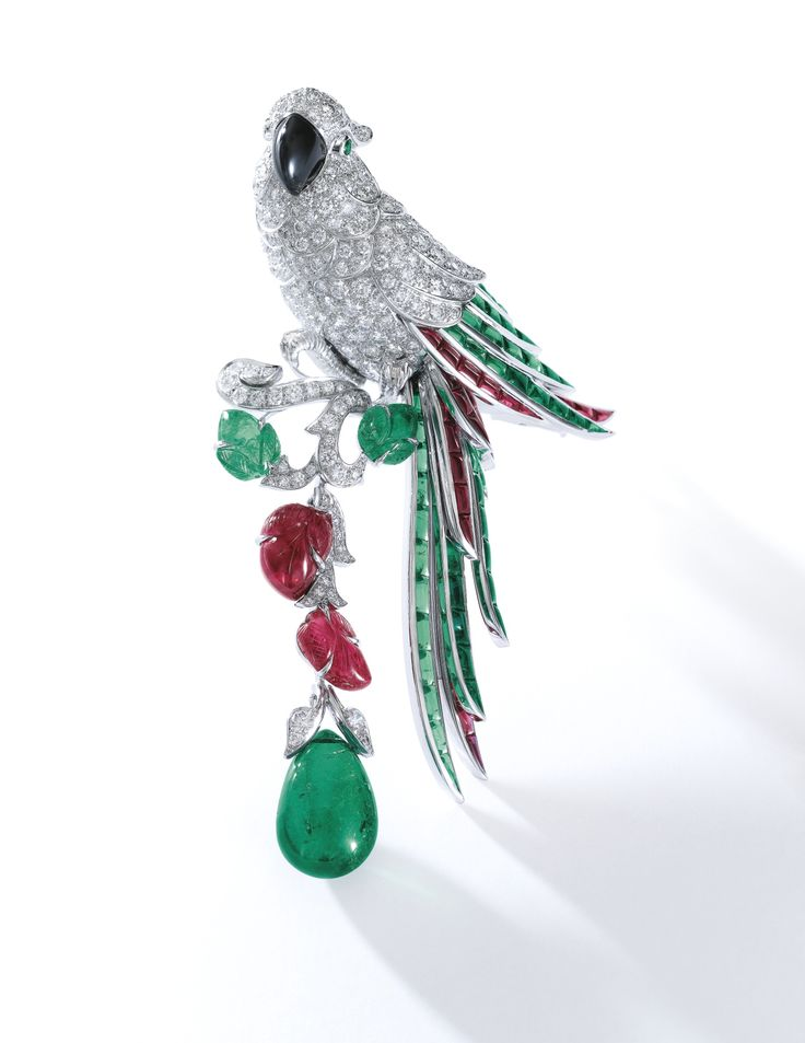 Emerald, ruby, mother-of-pearl and diamond brooch, 'New Khandy', Cartier - Estimate $306,959 - 509,865.  Designed as a parrot on a branch, set with brilliant-cut diamonds, polished mother-of-pearl, calibré-, circular-cut and carved emeralds and rubies, suspending a drop-shaped emerald weighing 11.55 carats, signed Cartier, numbered, French assay and maker's marks, case signed Cartier. (=)