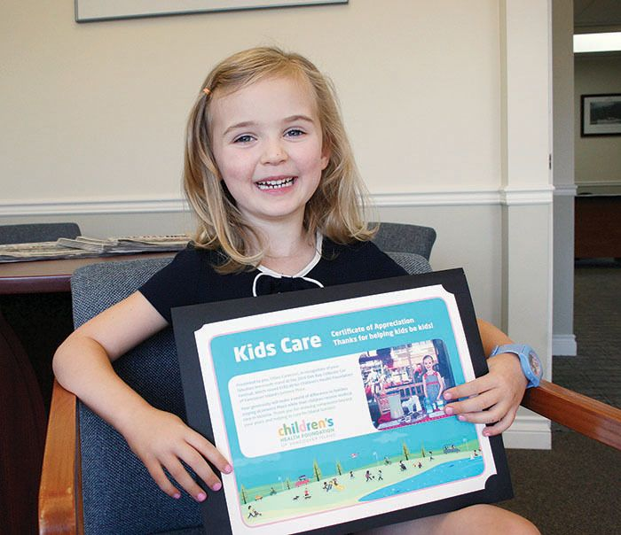 Chloe Cameron, 4, with a certificate from the Children's Health Foundation of Vancouver Island as thanks for her donation. The youngster raised $183.40 with a lemonade stand during the Oak Bay Collector Car Show with a little help from the Red Art Gallery!