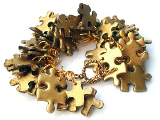 Oryginalna bransoletka wykonana z puzzli.  Elementy metalowe w kolorze złotym.  Długość 19,5cm