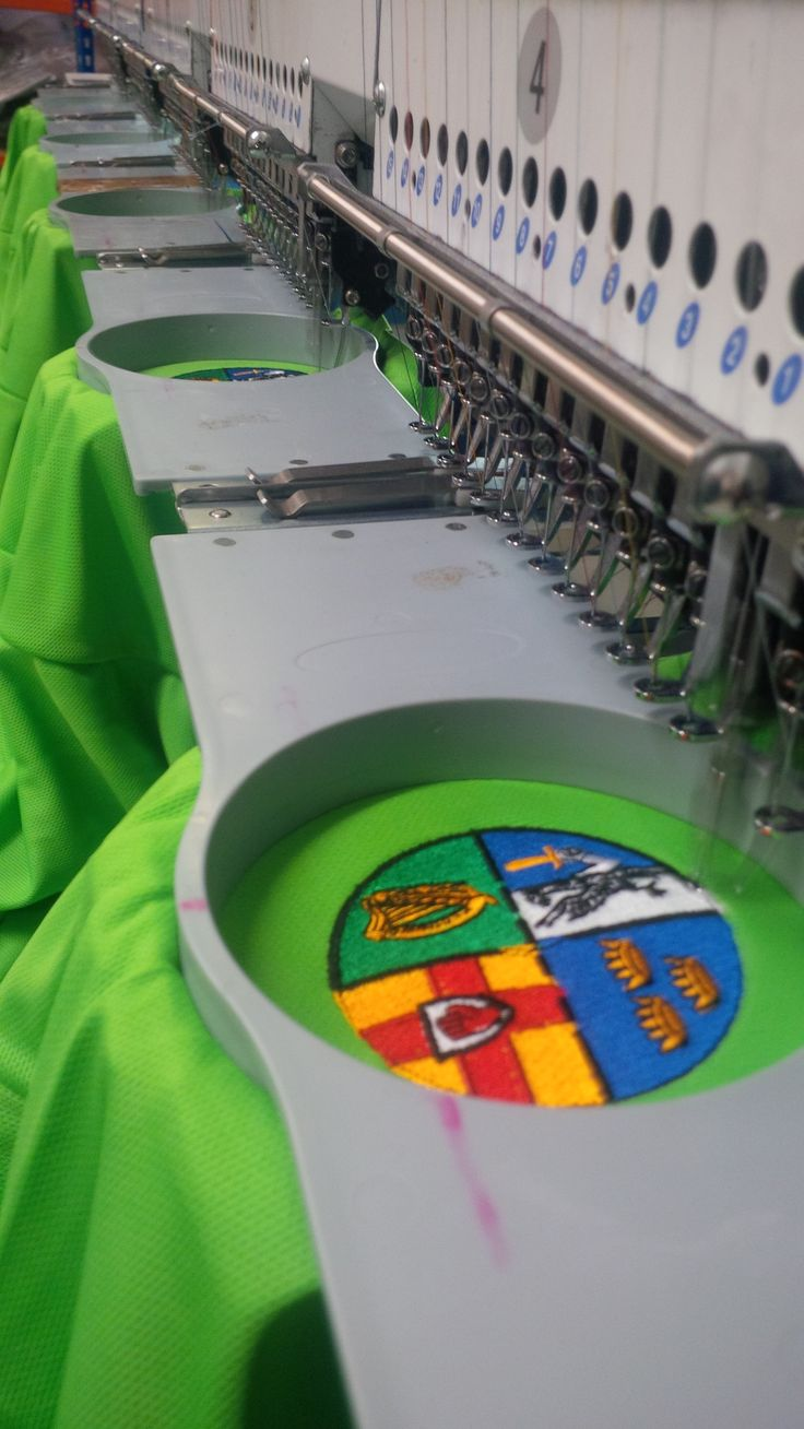 Embroidery process in action using an embroidery machine that is controlled with a computer that will embroider stored patterns, these may have multiple heads and threads as seen here.