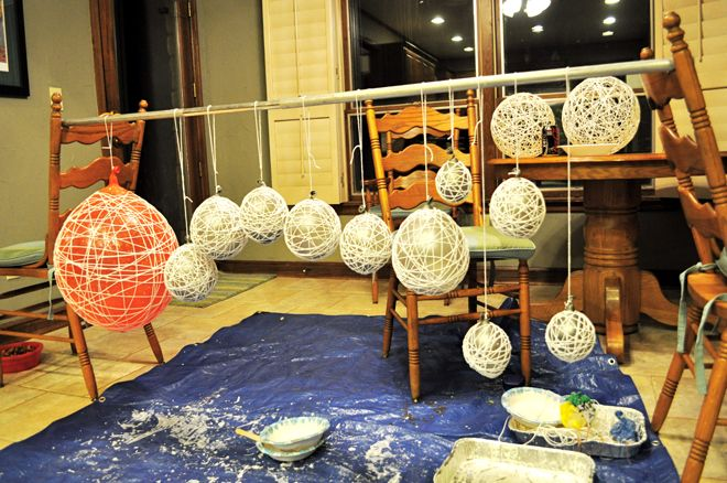 This site has the directions on how to make hanging balls.   Gather up:  Big balloon  Sharpie  Scissors  Cotton yarn  4 oz. White school glue  1/2 cup of Corn starch  1/4 cup of Warm water  Something to stir with  Petroleum jelly  Clear fast drying spray paint  Hanging lamp cord or fishing line (depending on your desired final product)  Container for mixing