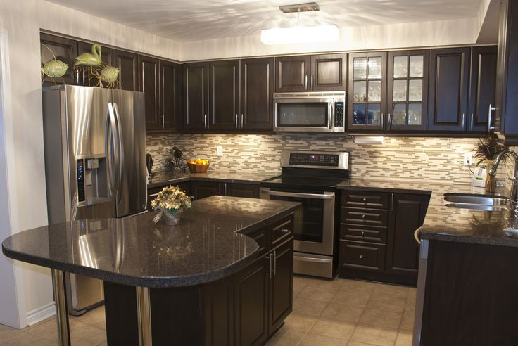 Beautiful dark wood kitchen with dark countertops and stainless steel appliances.