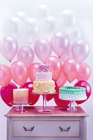 Create a dynamic backdropby arranging weighted helium balloons in different hues, with the darkest nearest the table