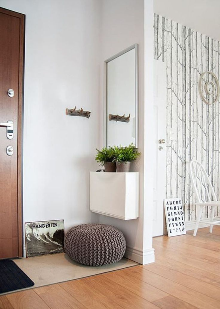 Minimalista, este apartamento utilizou nem o espaço apertado do hall - um espelho retangular, móvel pequeno, pufe e tapete recepcionam as visitas