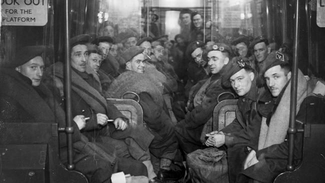 A group of soldiers are photographed in 1945, returning from Europe after D-Day on a London Underground train.