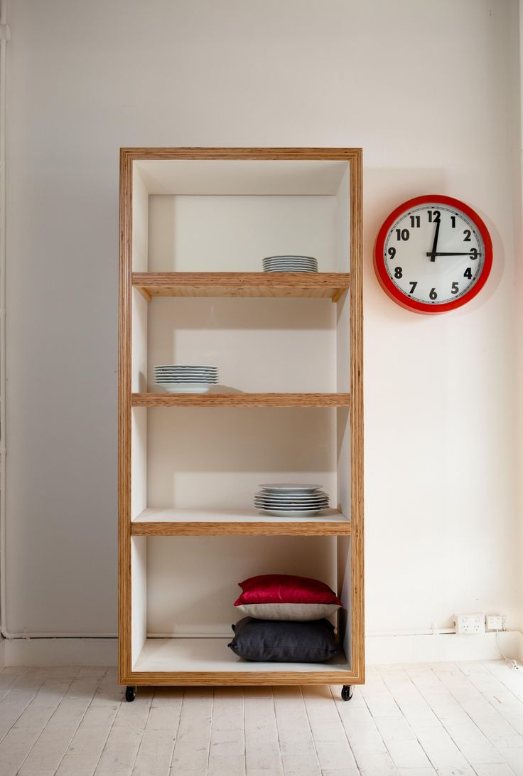Modern, clean, style,chunky movable shelving made from plywood, painted white and siting on castors. great for the kitchen.