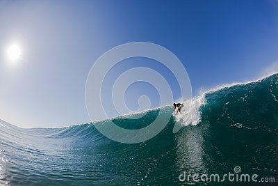 Surfer catching wave about to drop down large face getting the adrenaline rush.
