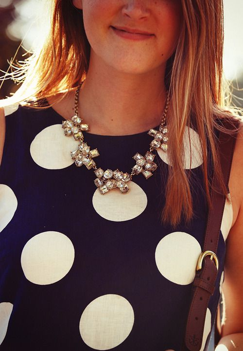 Polka dot dress with a crystal statement necklace.