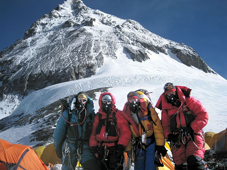 IMG climbers on the South Col with the Triangular Face (the first part of the summit climb) behind them.