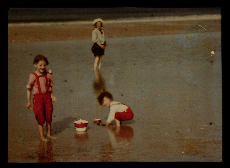 Drie kinderen spelend aan het Noordzeestrand, anoniem, 1907 - 1930