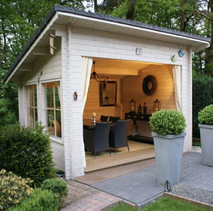 Gartenhaus mit Gardinen statt Tür, das geeignet für Abendessen ist