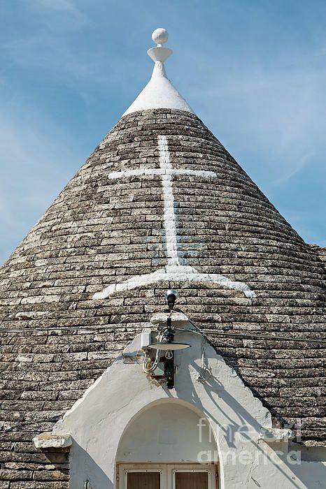 Symbol in the Trullo conical rooftop in Alberobello under a blue sky, Apulia, Italy