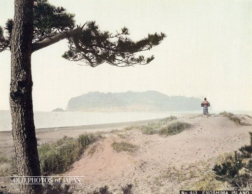 1890's. View From Katase. The island of Enoshima in Sagami Bay, Kanagawa Prefecture as seen from the dunes on shore. A reach of sand stretching from the beach to the island can be seen to the left of the man with his back to the camera. The tiny island with a circumference of just 4 km was connected to the mainland during low tide, but could only be reached by boat during high tide.