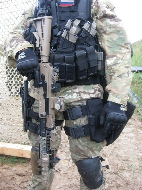 Russian Special Forces. With a 5.45 AK with hinged dust cover, MBUS sights on a full length rail system, AIMPOINT micro, oversized charging handle, oversized selector, and adjustable AR type stock.