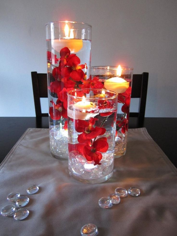 Glasvasen in unterschiedlichen Höhen mit Schwimmkerzen und Blumen