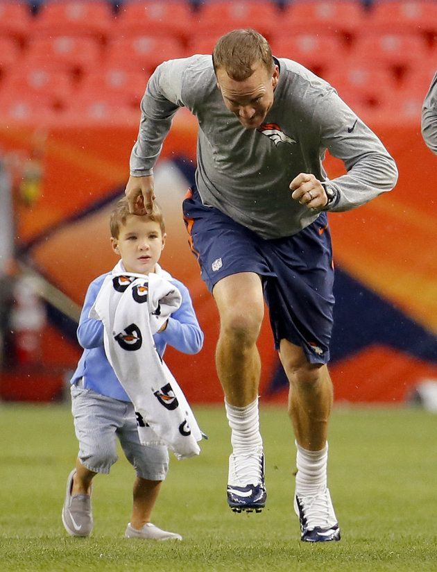 Peyton Manning warms up with his son. Quarterbacking kind of runs in the family.