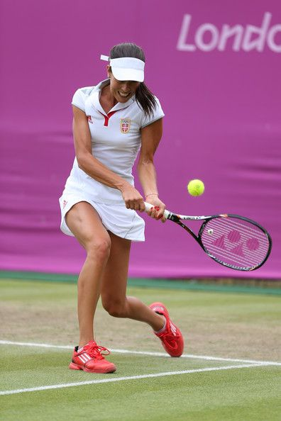 Ana Ivanovic Photos Photos - Ana Ivanovic of Serbia plays a backhand in her third round Women's Singles Tennis match against Kim Clijsters of Belgium during Day 5 of the London 2012 Olympic Games at Wimbledon on August 1, 2012 in London, England. - Olympics Day 5 - Tennis