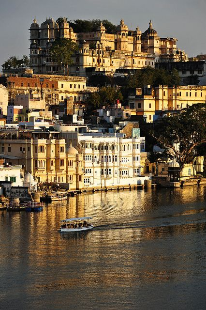 Last bit of sunlight illuminates the town of Udaipur, with Udaipur Palace at the top. India  ( by marc_guitard on Flickr)