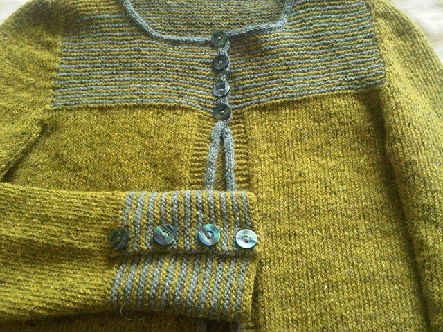 Cria by Redspinner, via Flickr. Pale olive with dusty blue / olive yoke and cuff and pale blue shell buttons.