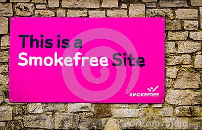 A bright pink wall plaque, located in a public place reminding people that they are in a zone where smoking is prohibited.