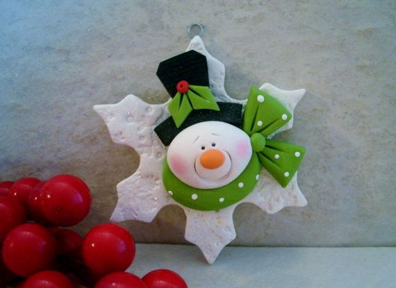 A whimsical snowman on a frosty snowflake! This is an original design that has been handcrafted from polymer clay. The ornament measures approximately 3 in diameter. All parts have been secured with liquid polymer for increased strength and the piece was lightly glazed with a