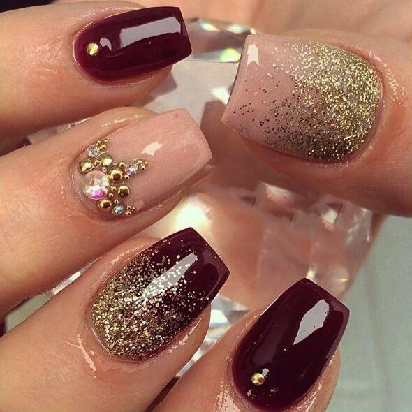 Uñas de color ciruela con dorado y piedras                                                                                                                                                                                 More